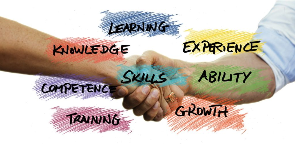 Hands Shaking behind the words learning, knowledge, experience, skills, competence, ability, training, and growth