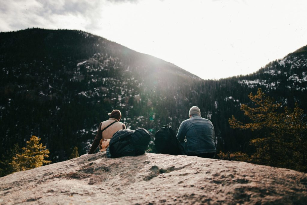 two people sitting in the mountains