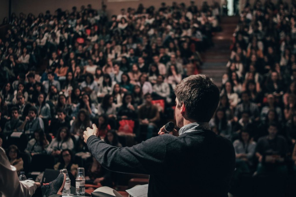 Person speaking to large audience in auditorium