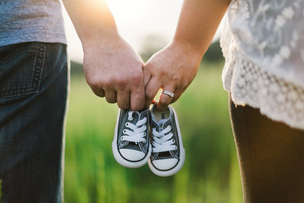father and mother holding baby shoes