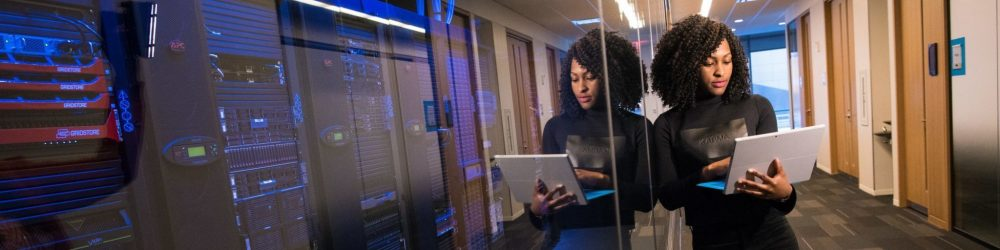 African American woman working on laptop, leaning against glass wall of a server room.