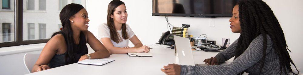 Three women talking at desk
