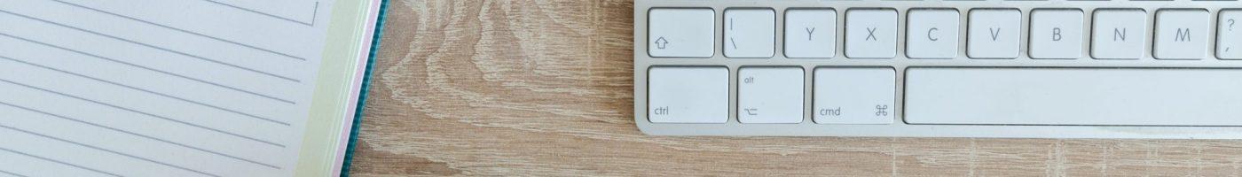 keyboard, headphones, coffee mug, and notebook on desk